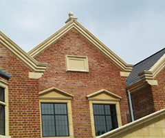 Building showing decorative stone gable, copings, namestone and window surrounds.